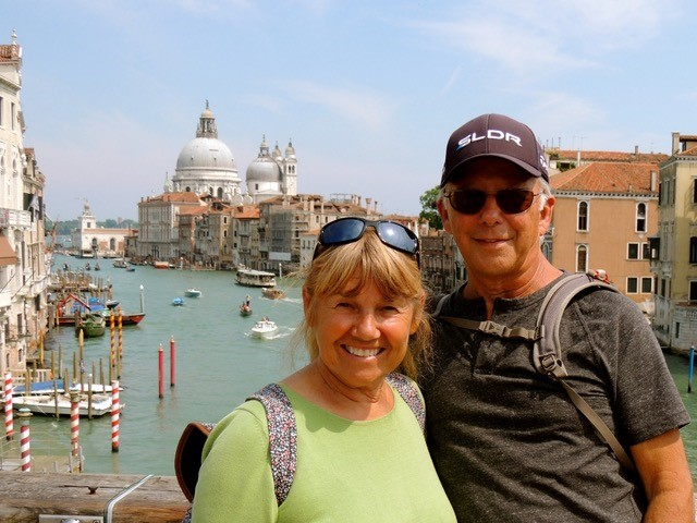Allan and Margrit stand together on a bridge in Italy.